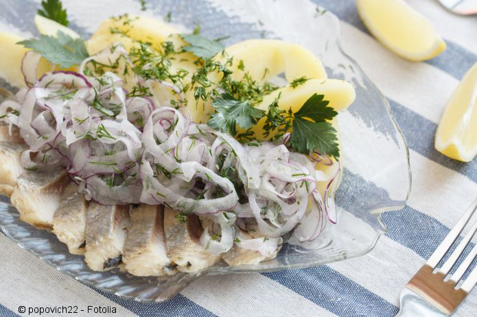 Herring with onion on a plate in the form of fish